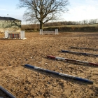 Outdoor arena split into a jumping area and a dressage/ schooling area.
